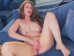 Wavy hair beauty relaxes on the couch and masturbates her box